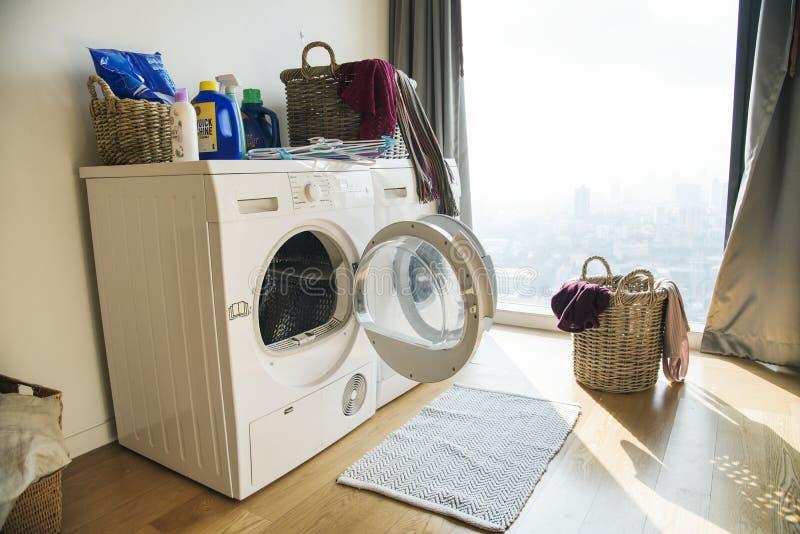 Waschmaschine mit schmutzigem Kleidungskorb lizenzfreie stockfotografie