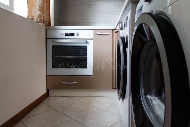 Waschmaschine und Ofen in der Küche lizenzfreies stockbild