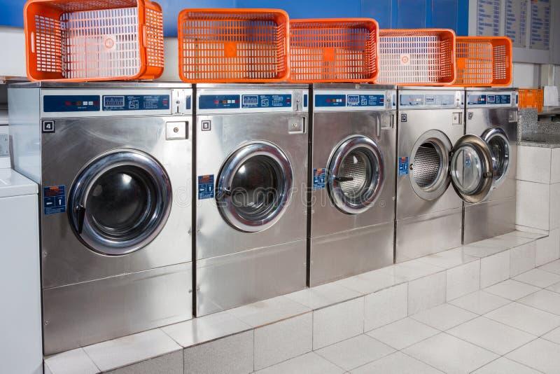 Waschmaschinen und leere Körbe in Folge stockbilder