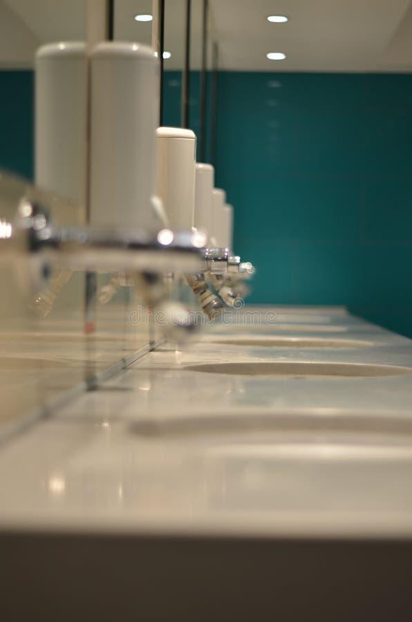 Waschraum mit einigen Waschbecken und Seifenspendern stockbild
