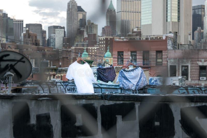 Waschtag in New York City, Kleidung, die auf einer Manhattan-Dachspitze unter Graffiti und Wolkenkratzern trocknet lizenzfreie stockfotos