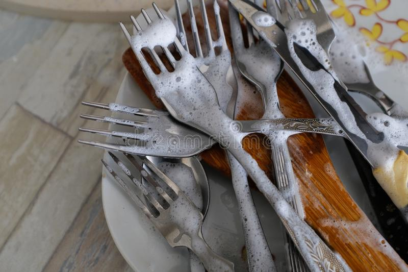 Wash dirty dishes: forks and plates with a pattern in soapy water in the kitchen sink stock photography