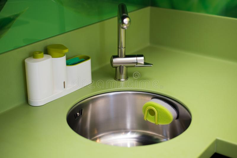 Wash dishes beautifully sponge green in the kitchen cleanliness. Of the faucet stock photo