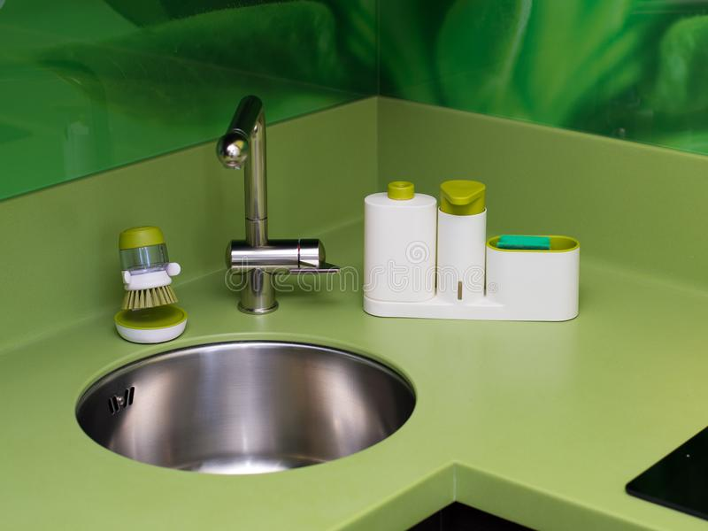 Wash dishes beautifully sponge green in the kitchen cleanliness. Of the faucet stock image