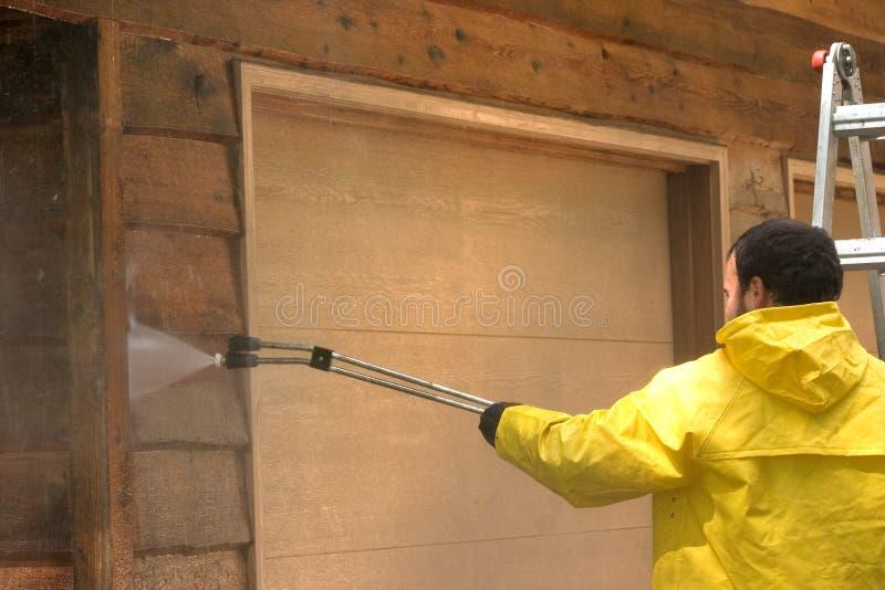 Wash It Down. A man pressure washing a wood sided garage royalty free stock photo