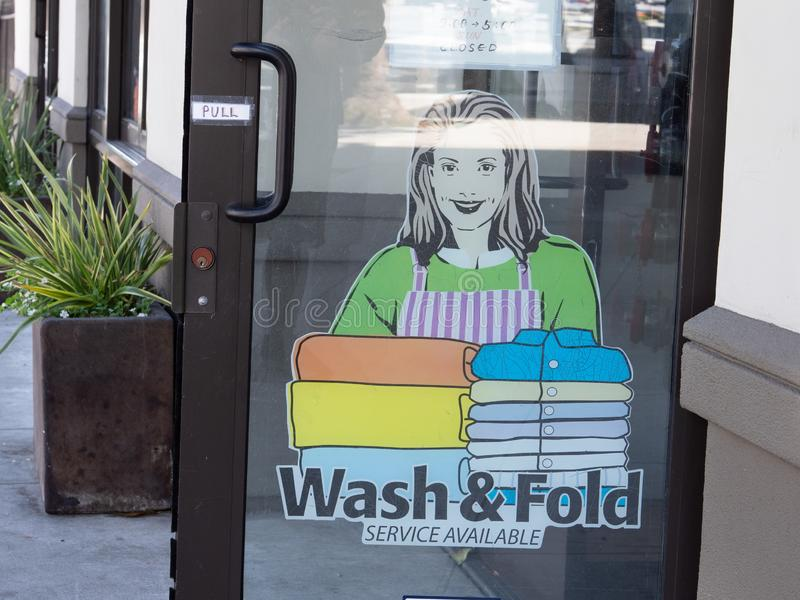 Wash and fold service available sign posted outside laundromat door. Wash and fold service available sign posted outside a laundromat door stock photos