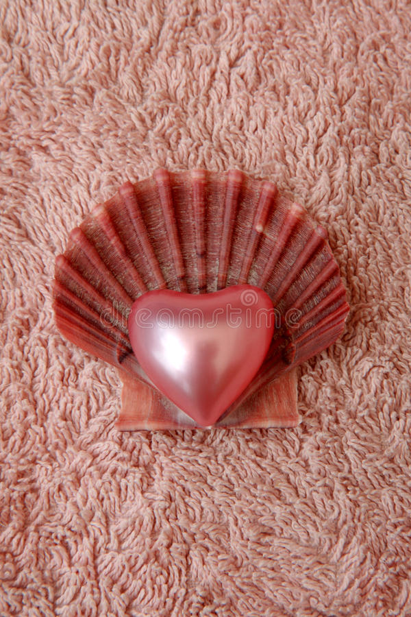 Wash-lovely. Hotel room service decoration, pink bath towel, heart shaped bath pearl and shell stock photo