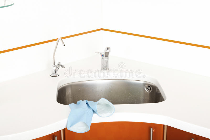 Washbasin, blue rubber gloves and chrome faucets