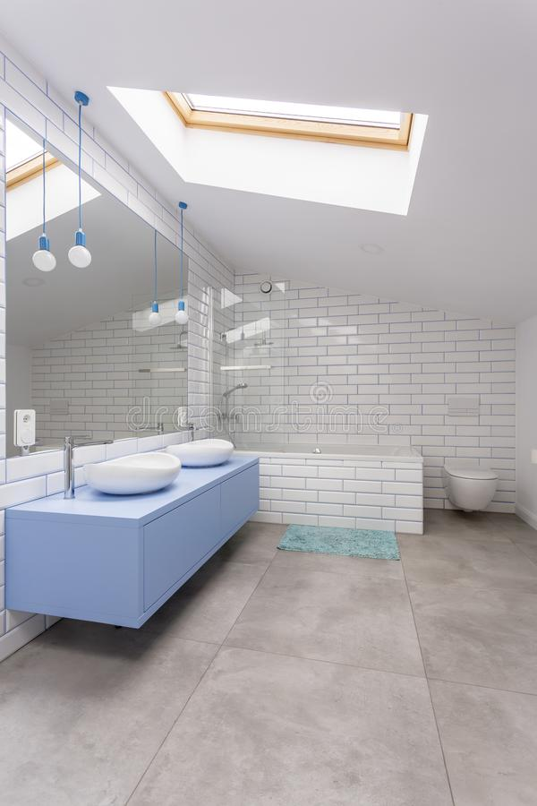 Blue bathroom with brick wall. Washbasin cabinet mirror and light bulbs in blue bathroom with white brick wall stock image
