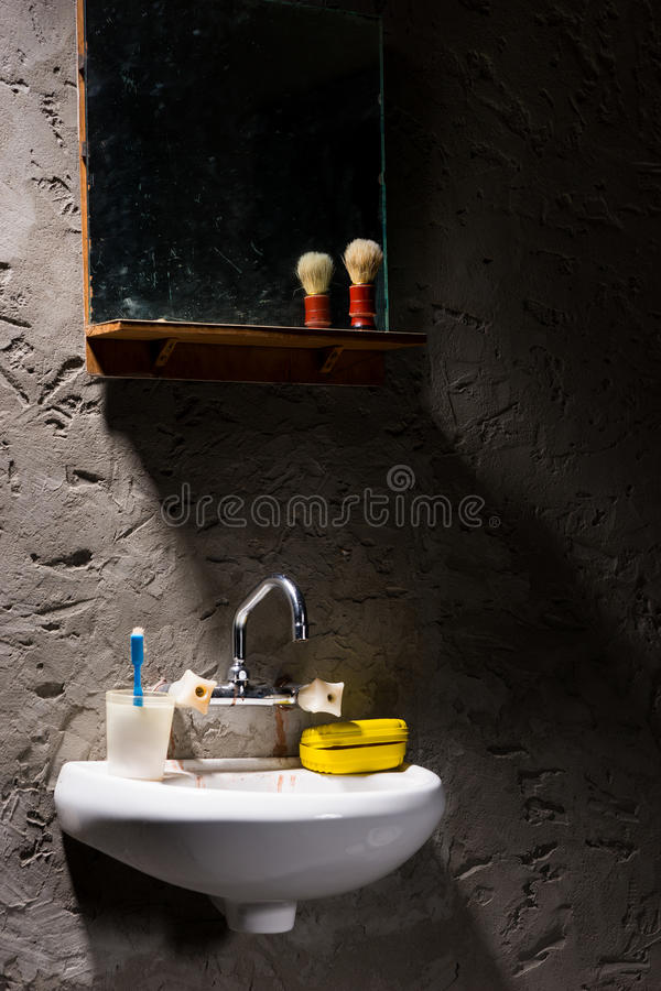 Washbasin with a glass for a toothbrush and a soap box on it under the mirror in a prison cell royalty free stock images