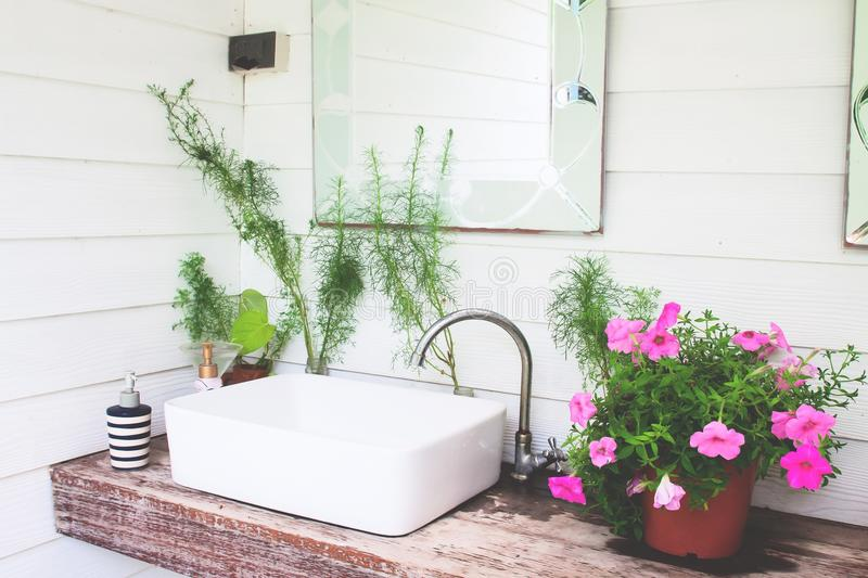 Washbasin with pink flowers in home garden, White and beautiful. Concept stock image