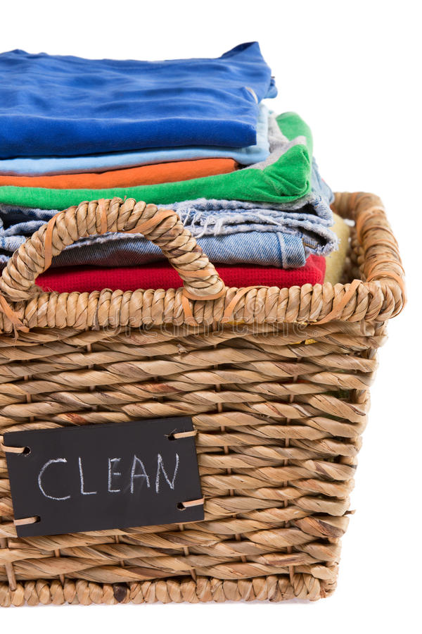 Washed fresh clean clothes in a laundry basket. Close up view of washed fresh clean clothes neatly folded and stacked in a rustic wicker laundry basket with a royalty free stock images