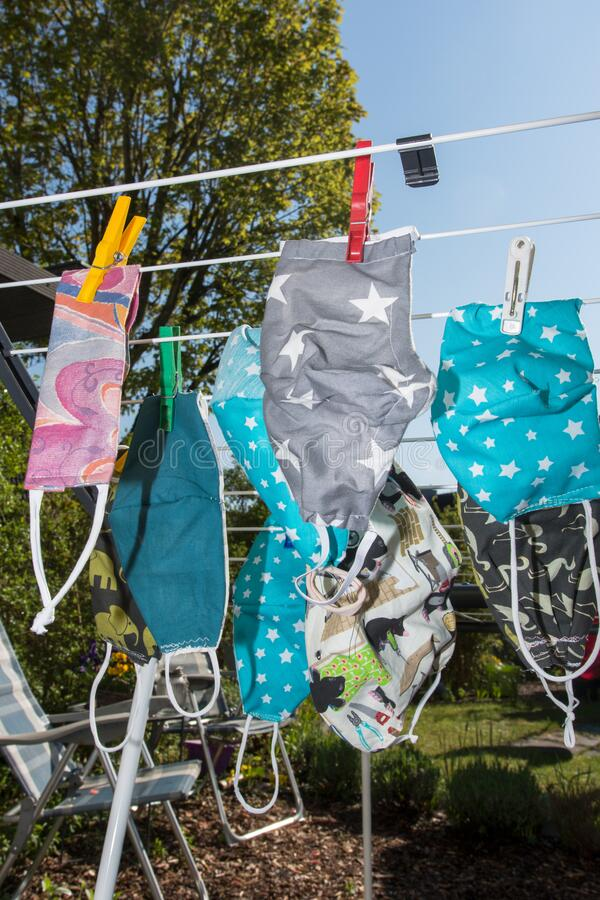 Handmade protection masks on a clothes line stock photo