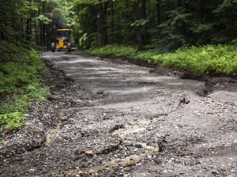 Water Damage of Dirt Road. A washed out and damaged rural dirt road from rain and weather being repaired by road equipment in background royalty free stock images