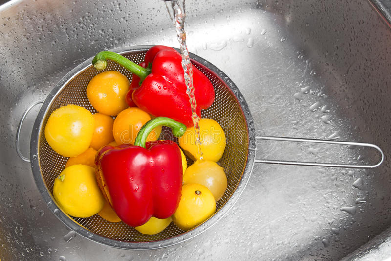 Washing colorful fruits and vegetables. In the kitchen sink stock image