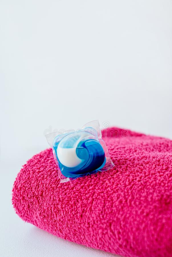 Washing detergent capsule pods and pink towel stock photos