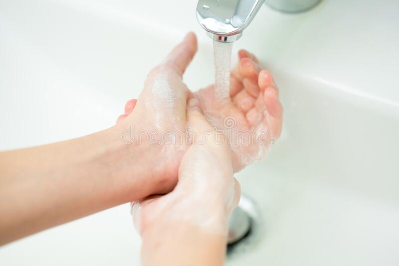 Washing of female hands with soap in bathroom stock images