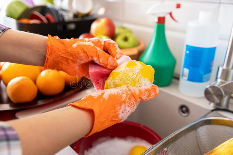 Washing fruits in the kitchen with water and detergent or soap. COVID-19 Coronavirus pandemic concept. royalty free stock image