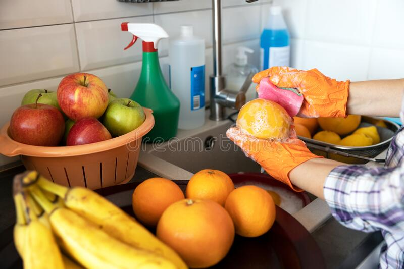 Washing fruits in the kitchen with water and soap or detergent. COVID-19 Coronavirus pandemic concept. royalty free stock photo