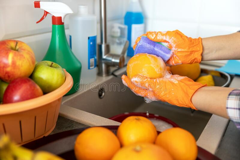 Washing fruits in the kitchen with water and soap or detergent. COVID-19 Coronavirus pandemic concept. stock images