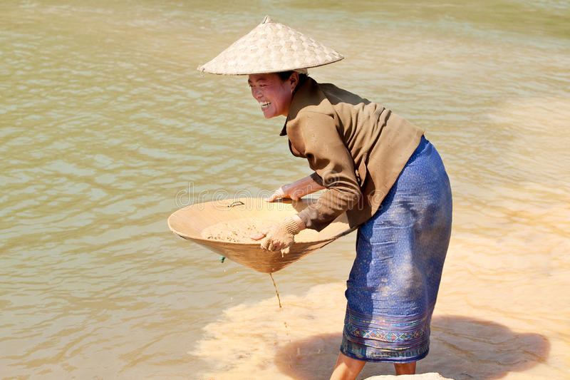 Washing gold in the river. Woman sieves rock at river Nam Ou in Laos royalty free stock photos