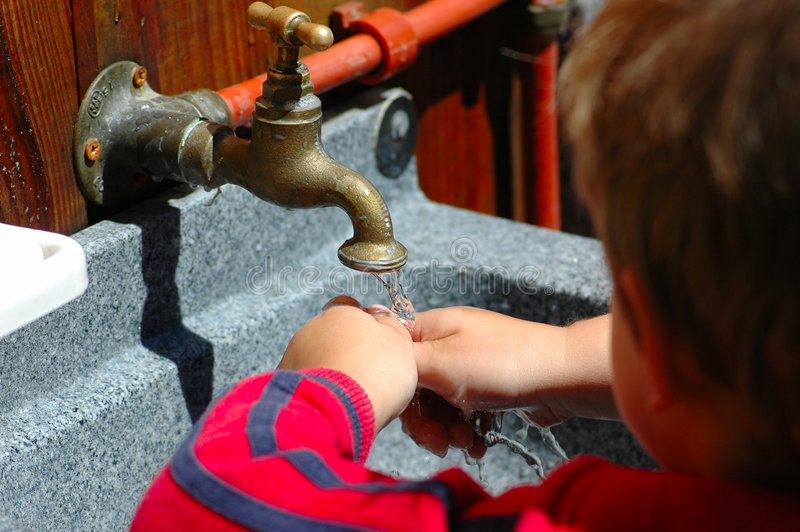 Washing hands. A cute little boy toddler washing hands with soap and water outdoors in the garden of the payschool stock photography