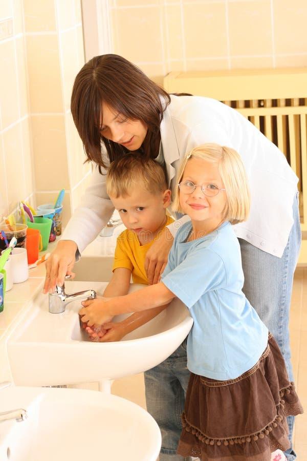 Washing hands. Preschoolers in bathroom washing hands royalty free stock photo
