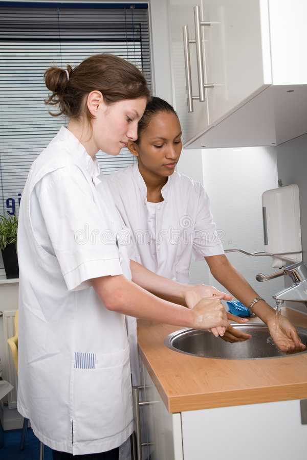 Washing hands. Two young medical students thoroughly washing their hands royalty free stock images