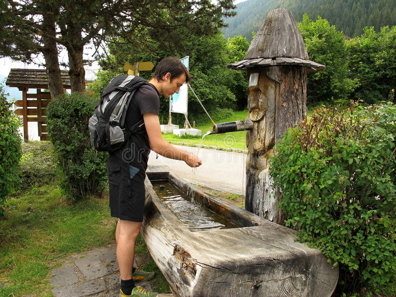 Washing hands at fountain. Young man with backpack washing hands at a wooden fountain royalty free stock photo