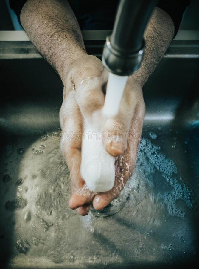 Washing hands in a sink with a bar of soap stock images