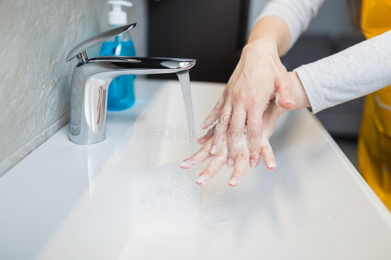 Washing hands under water tap in bathroom. Hygiene concept. Washing hands under the water tap or faucet. Hygiene concept detail. Beautiful hand and water stream stock image