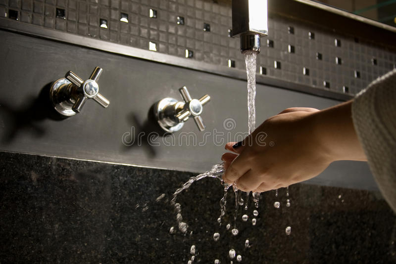 Washing hands. A woman washing hands in the bathroom stock photography