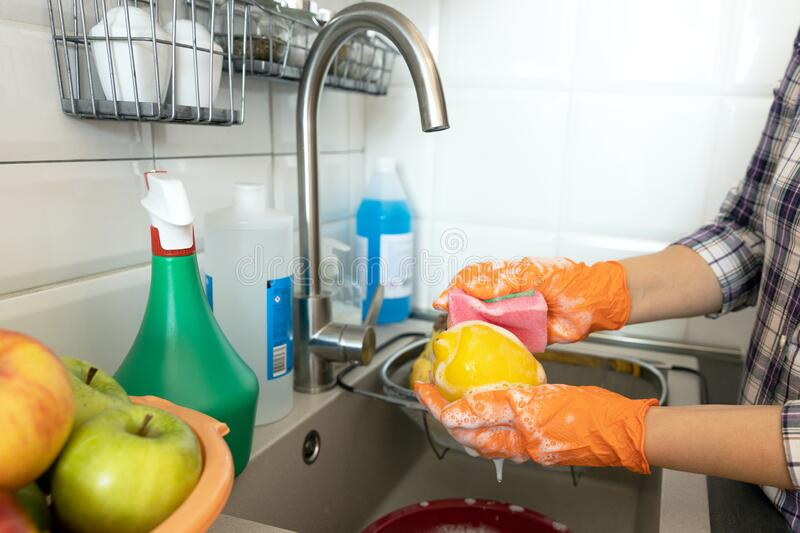 Washing lemon in the kitchen with water and soap royalty free stock image