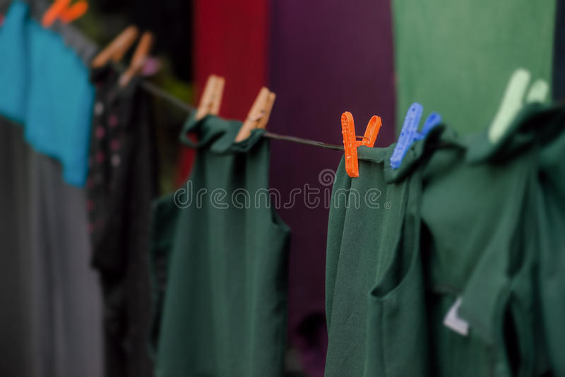 Washing line with clean dark clothes drying eco-friendly outdoors hanging stock images