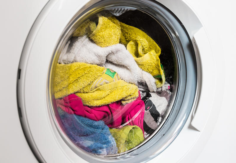 Washing machine door, clean colorful clothes, yellow, blue plush terry royalty free stock photos
