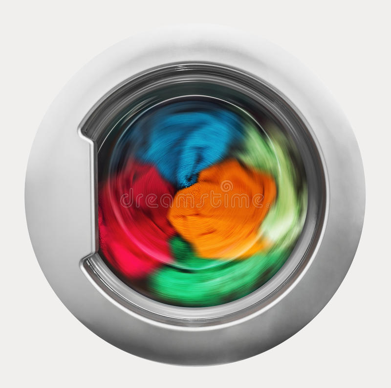 Washing machine door with rotating garments inside royalty free stock photography