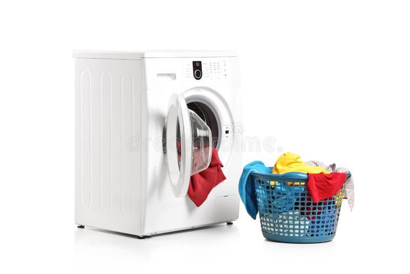 Washing machine and full laundry bin. A washing machine and full laundry bin isolated on white background stock photography