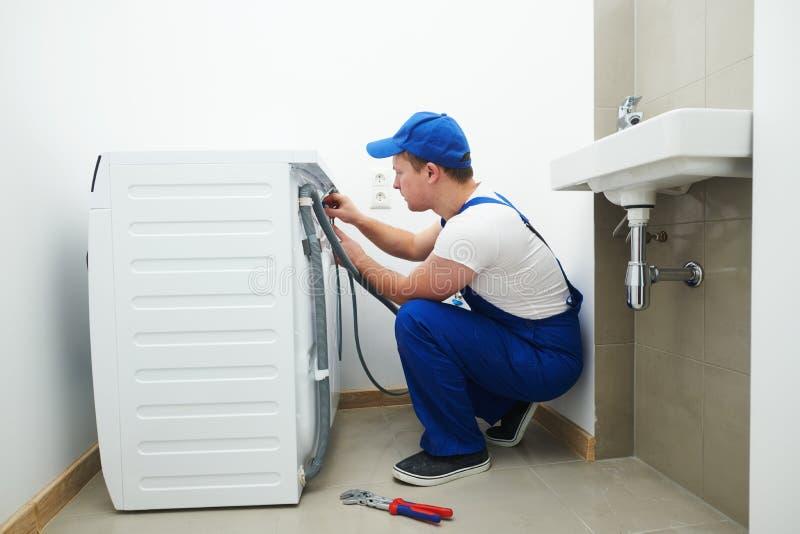 Washing machine installation or repair. plumber connecting appliance. Washing machine installation or repair service. plumber connecting appliance to water stock photos