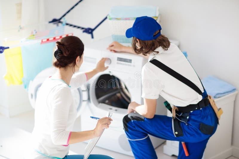 Washing machine repair technician. Washer service. Washing machine repair service. Young technician examining and repairing tumble dryer. Woman looking at stock photography