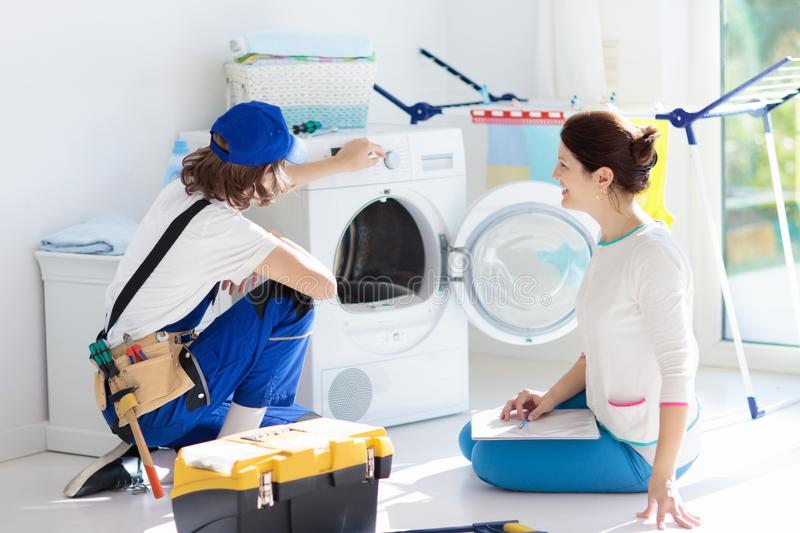 Washing machine repair technician. Washer service. Washing machine repair service. Young technician examining and repairing tumble dryer. Woman looking at stock images