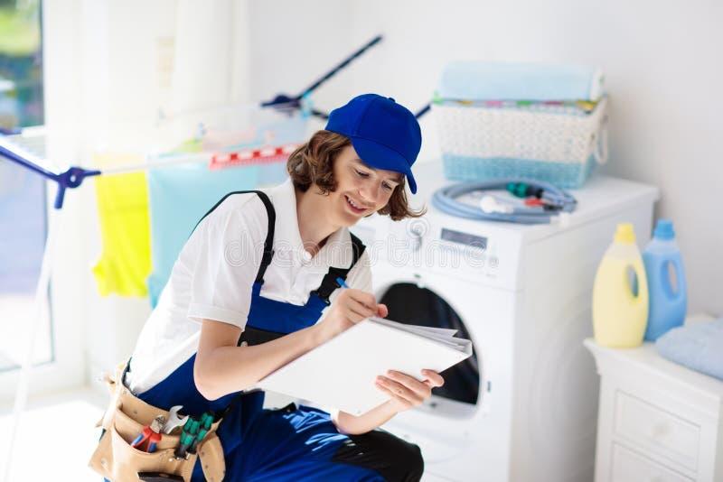 Washing machine repair technician. Washer service. Washing machine repair service. Young male technician in blue uniform examining and repairing broken washer or royalty free stock photo