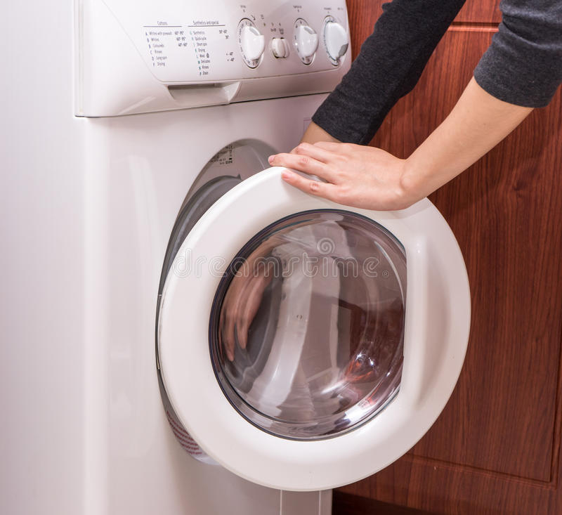 Washing machine with woman hands ,Open royalty free stock photo