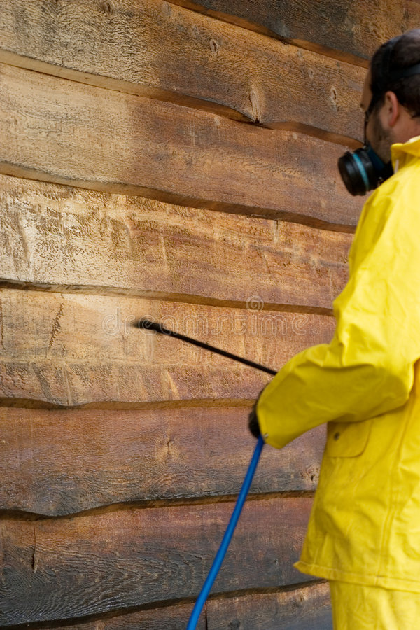 Washing the Siding. A man doing a chemical wash on the side of a garage royalty free stock image