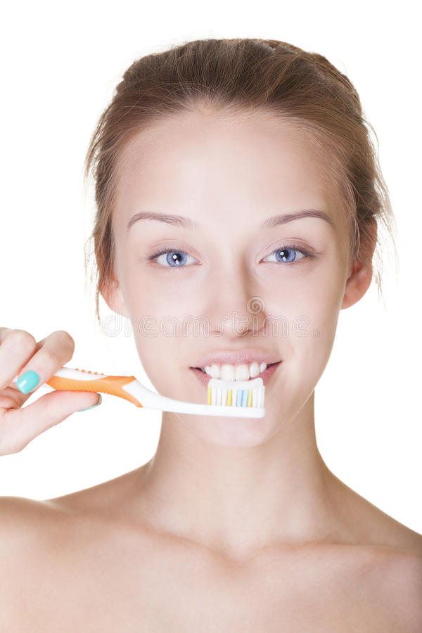 Washing teeth. Attractive smiling young girl washing teeth on isolated white royalty free stock images