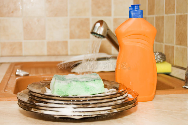 Washing up liquid with a sponge on kitchen royalty free stock image