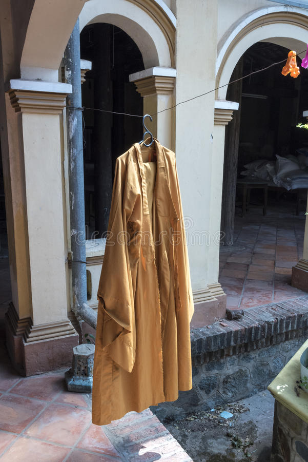 Washing in the Vinh Trang Temple. A newly washed monks robe in the Vinh Trang Temple in the Mekong Delta. All monks wear this orange coloured robe from when they stock photo