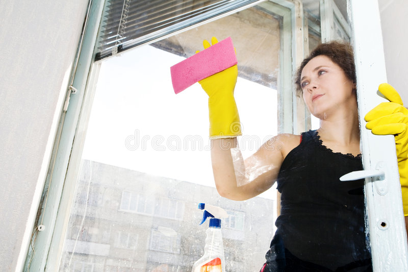 Washing window. An image of a woman washing the window royalty free stock photo