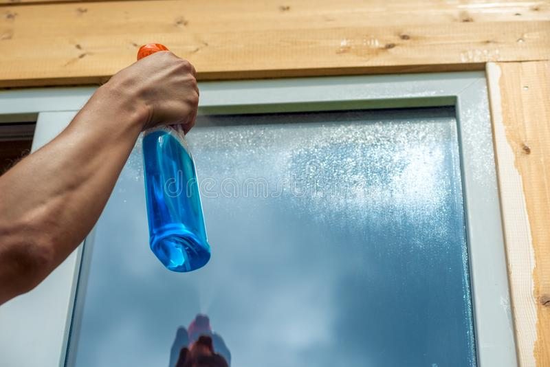 Washing window, closeup of spray cleaner in male hand on window stock photo