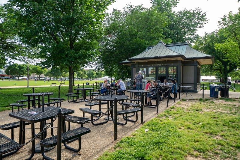 Washington, C.C. - 9 de maio de 2019: Os turistas que sentam-se em tabelas de piquenique apreciam o almo?o de uma constru??o do s fotografia de stock