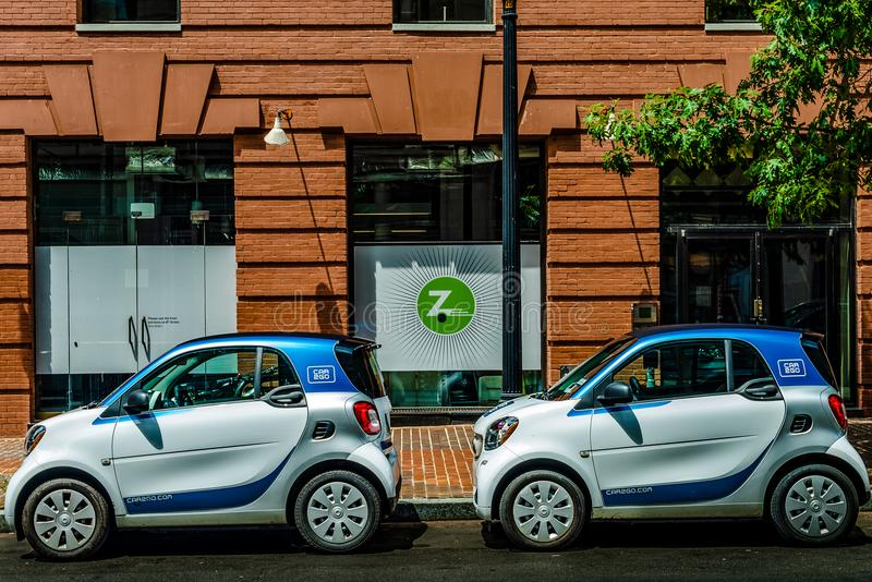Washington, D.C. - July 20, 2018: Car2Go cars parked in front of Zipcar office. Two Car2Go smartcars parked in front of local Zipcar office in Washington, D.C royalty free stock photography